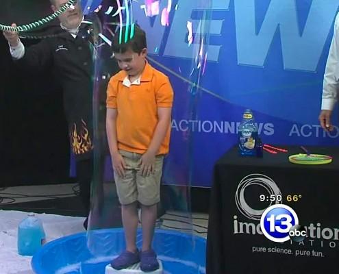 Chief Scientist Carl Nelson puts a boy inside a soap bubble.